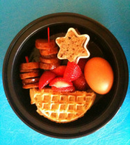 bento breakfast:  smoked sausage, strawberries, hard boiled egg, half ww waffle, piece of cereal bar in shape of star