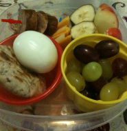 bento breakfast: muesli bread, grapes, hard boiled egg, banana and apple, cheese slices, smoked sausage